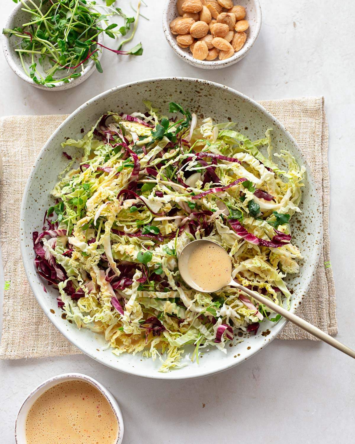 A serving bowl with shredded green cabbage and red cabbage tossed into a slaw.