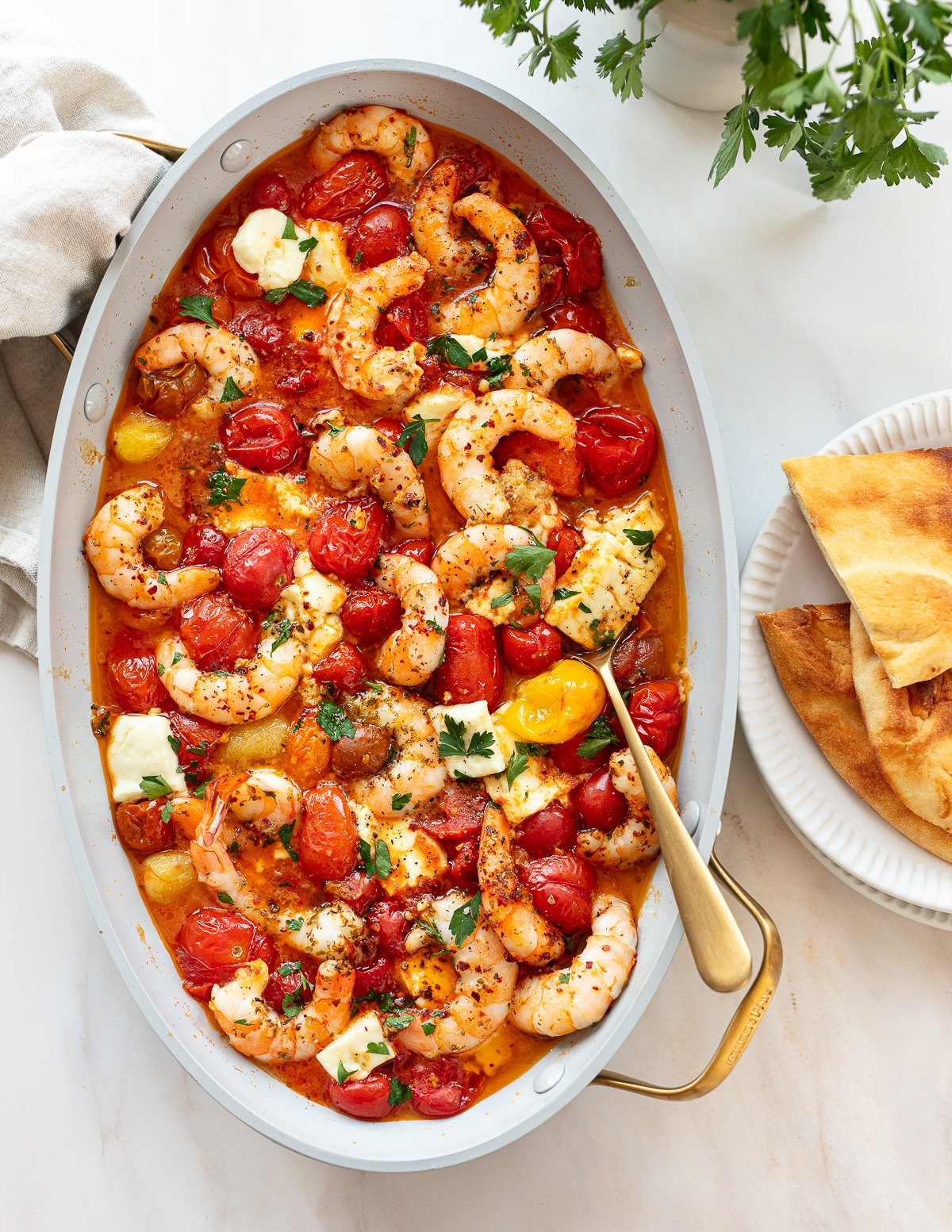An oval baking pan filled with baked shrimp with feta cheese and cherry tomatoes, with a serving spoon and pita bread on the side.
