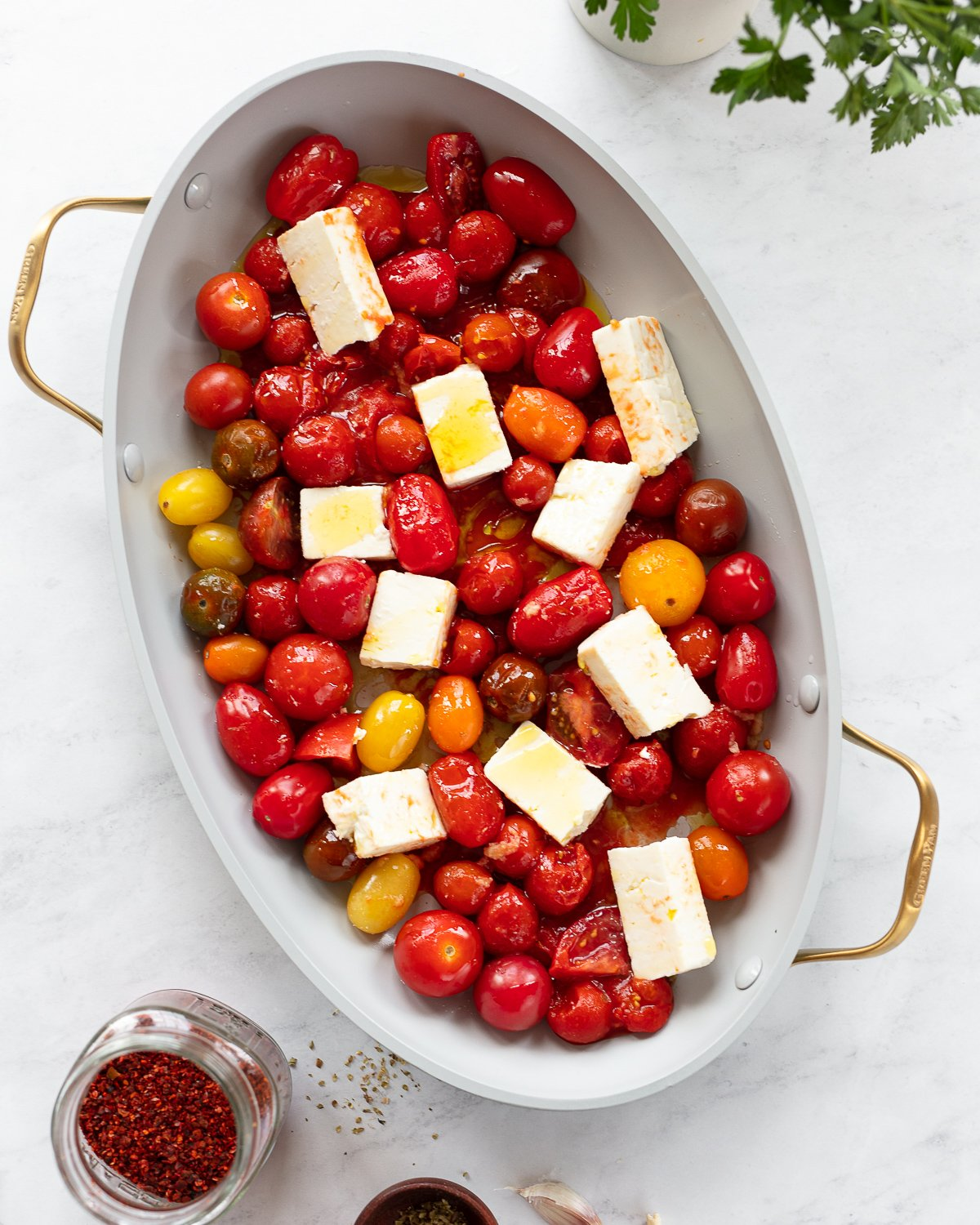 Cherry tomatoes and chunks of feta cheese in a baking dish ready for the oven.