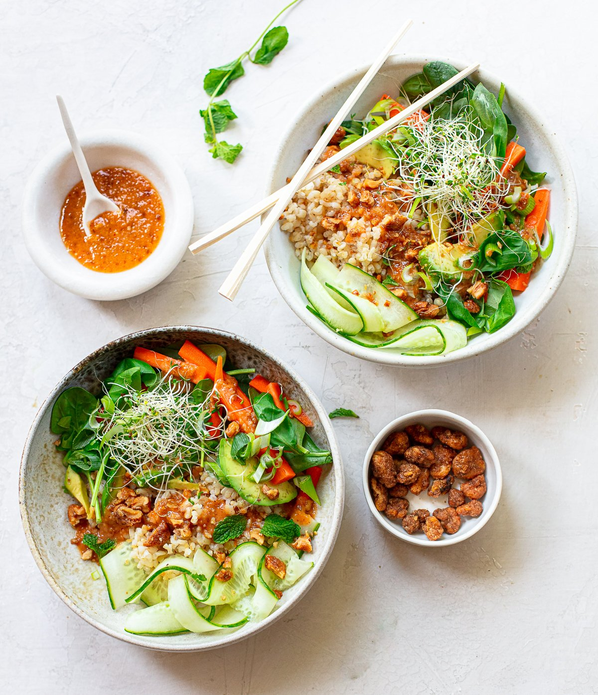 Two gray bowls with chopsticks, full of rice salad with avocado, cucumber, carrots and walnut sauce.