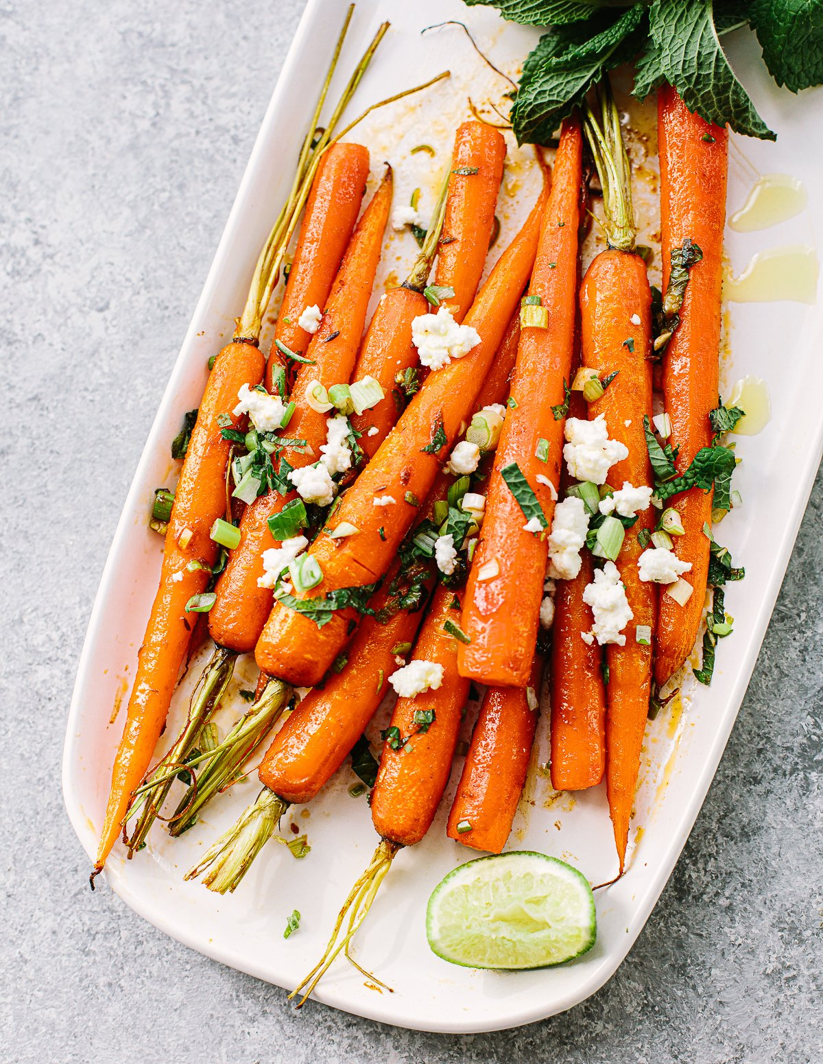 A bunch of roasted carrots on a white serving platter, topped with mint, lime and feta cheese.