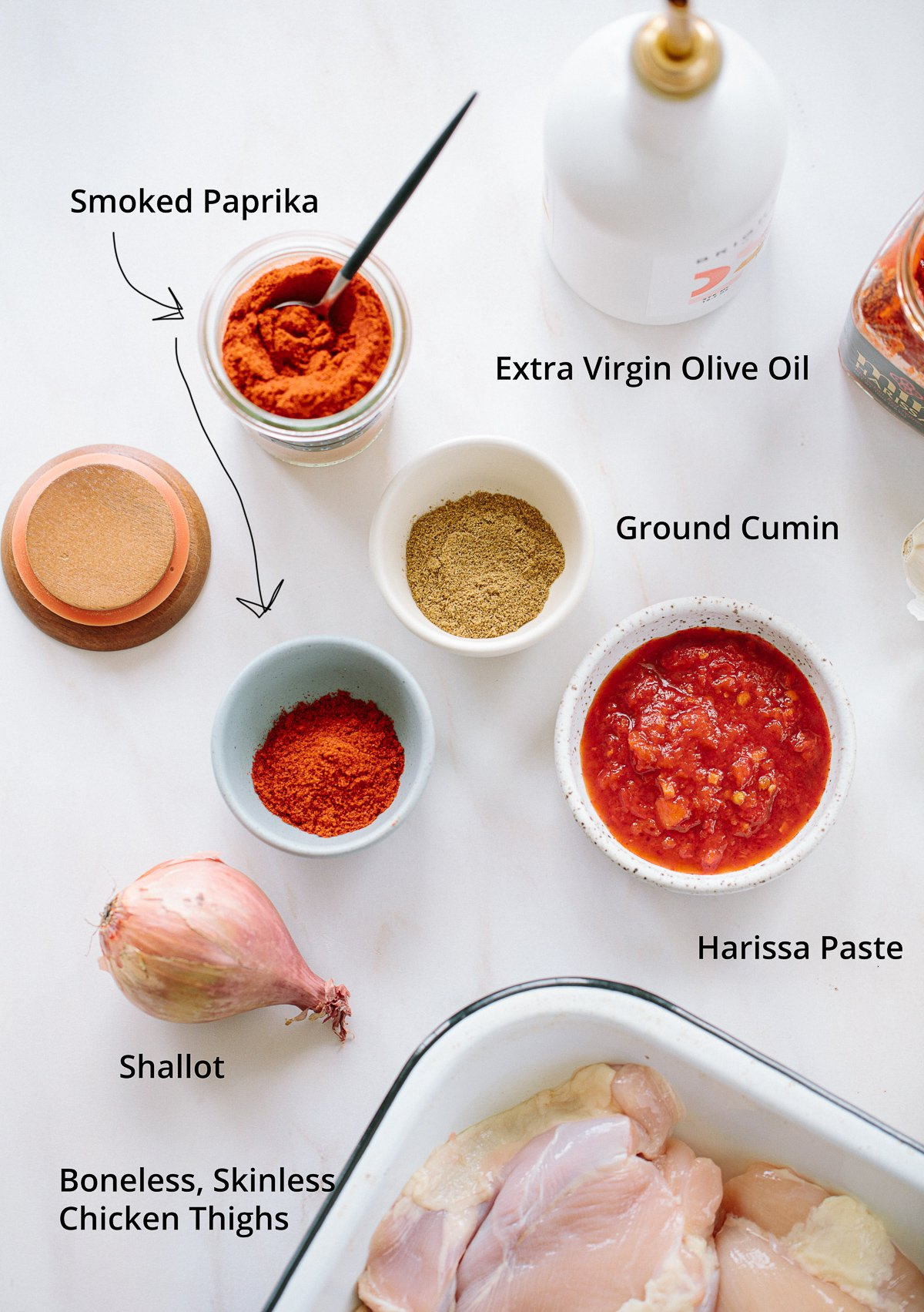 An overhead image of ingredients needed to make baked harissa chicken, with harissa paste, cumin and paprika in small bowls