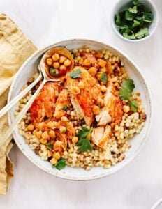 A bowl with a serving of baked chicken thighs with harissa sauce, pearl couscous and chickpeas with a gold napkin, spoon and fork.