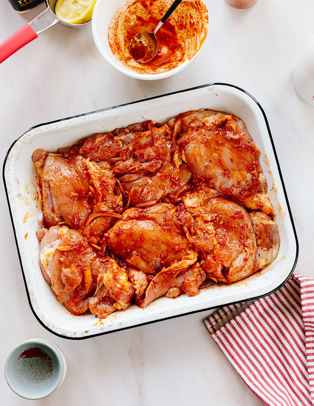 An overhead image of a baking pan with raw chicken thighs in a harissa marinade.