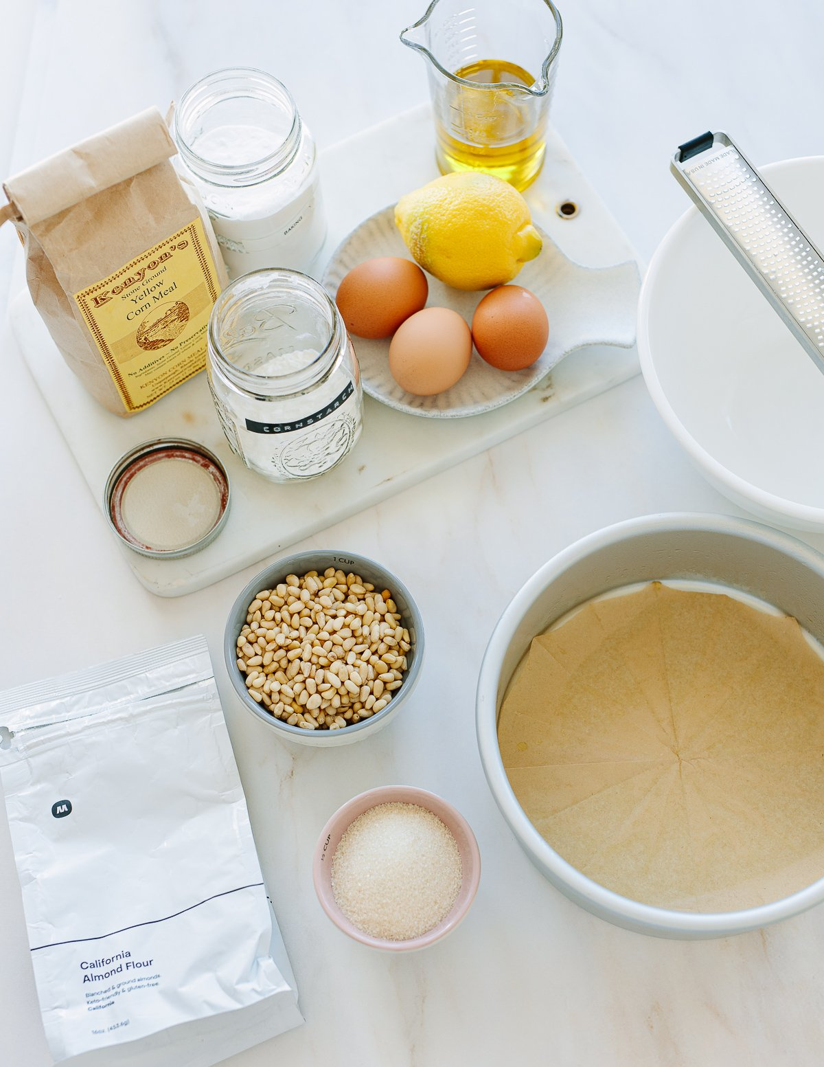 Ingredients for making a one-bowl lemon cake on a counter, including eggs, lemon, pine nuts, almond flour, cornmeal, sugar and olive oil.
