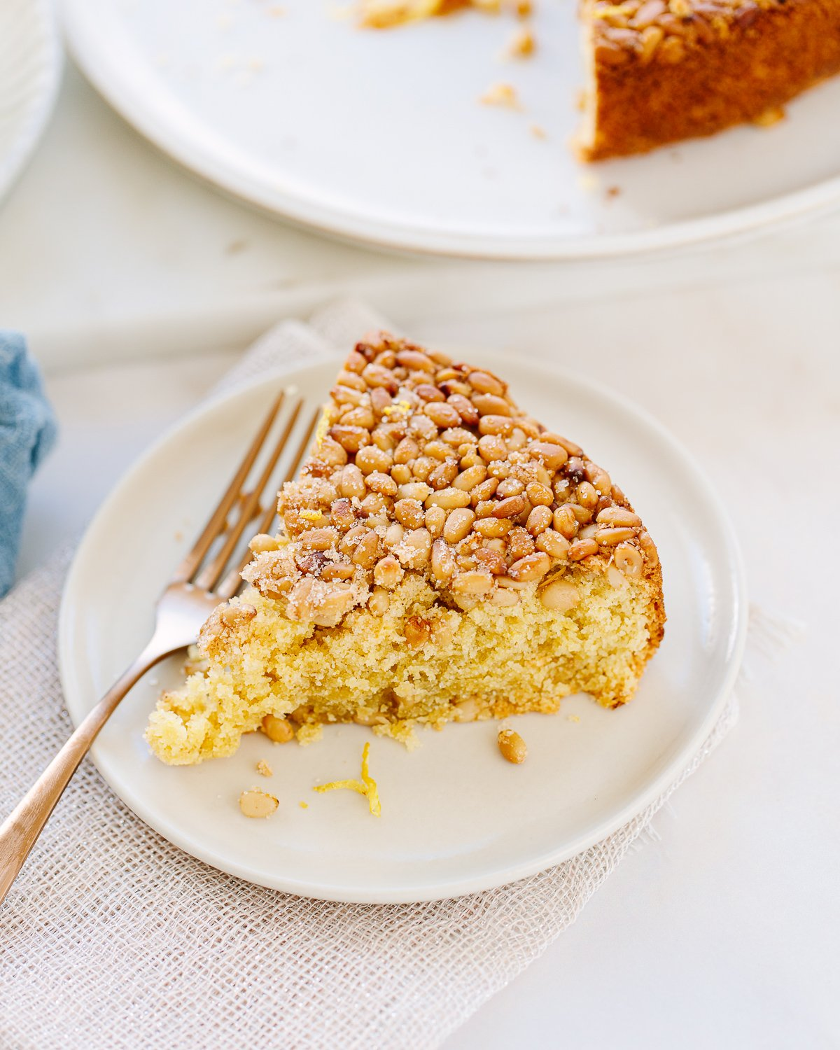 A wedge slice of lemon cake topped with pine nuts, on a cake plate with a fork on the side.