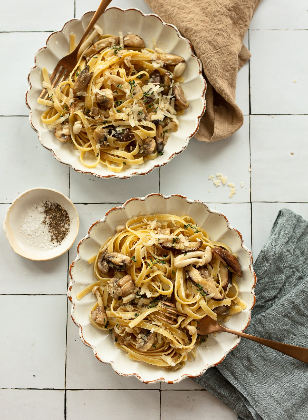 Bowls of fettuccine pasta topped with mushroom sauce, with cheese and forks