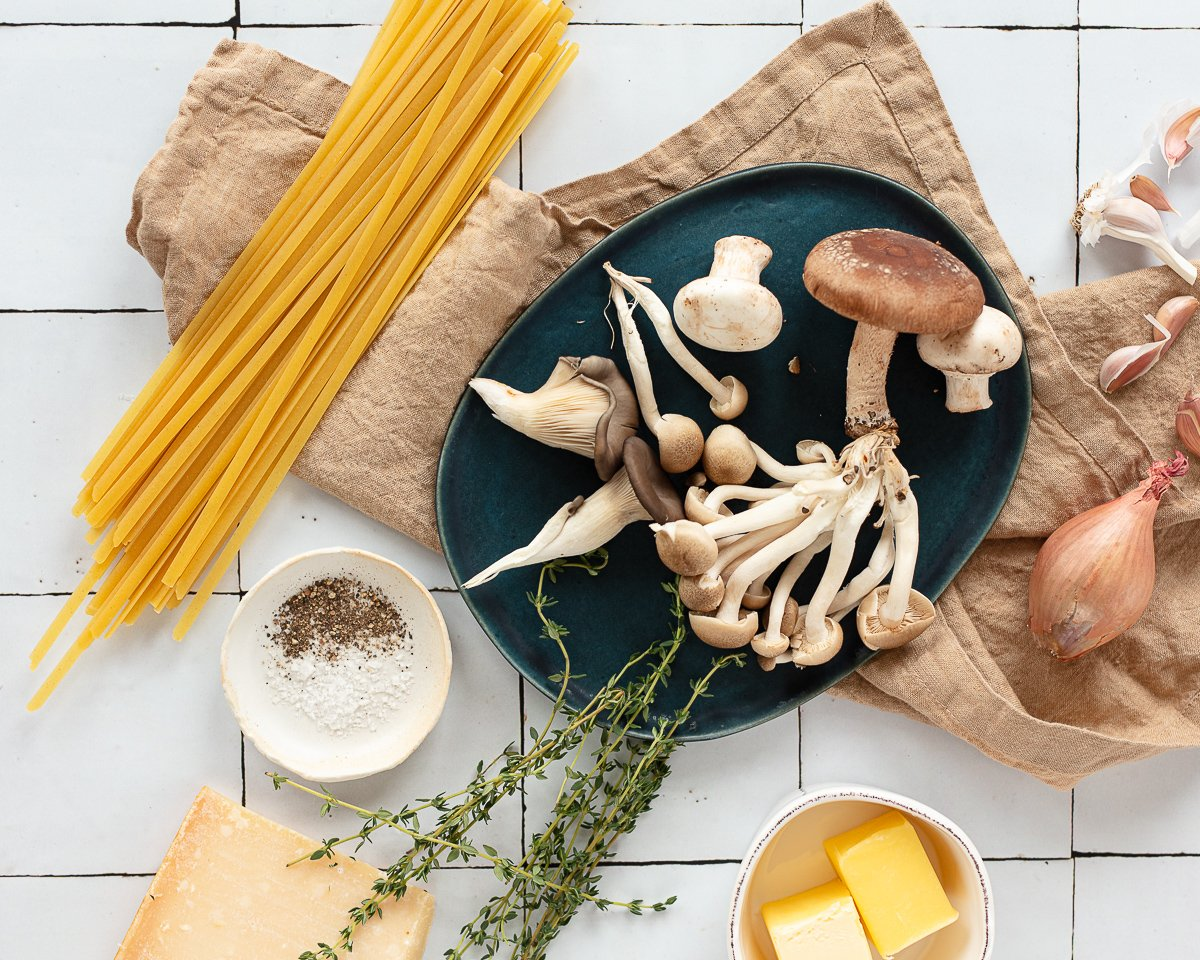 Assorted wild mushrooms on a counter with a linen towel, dry spaghetti, butter and Parmesan cheese.