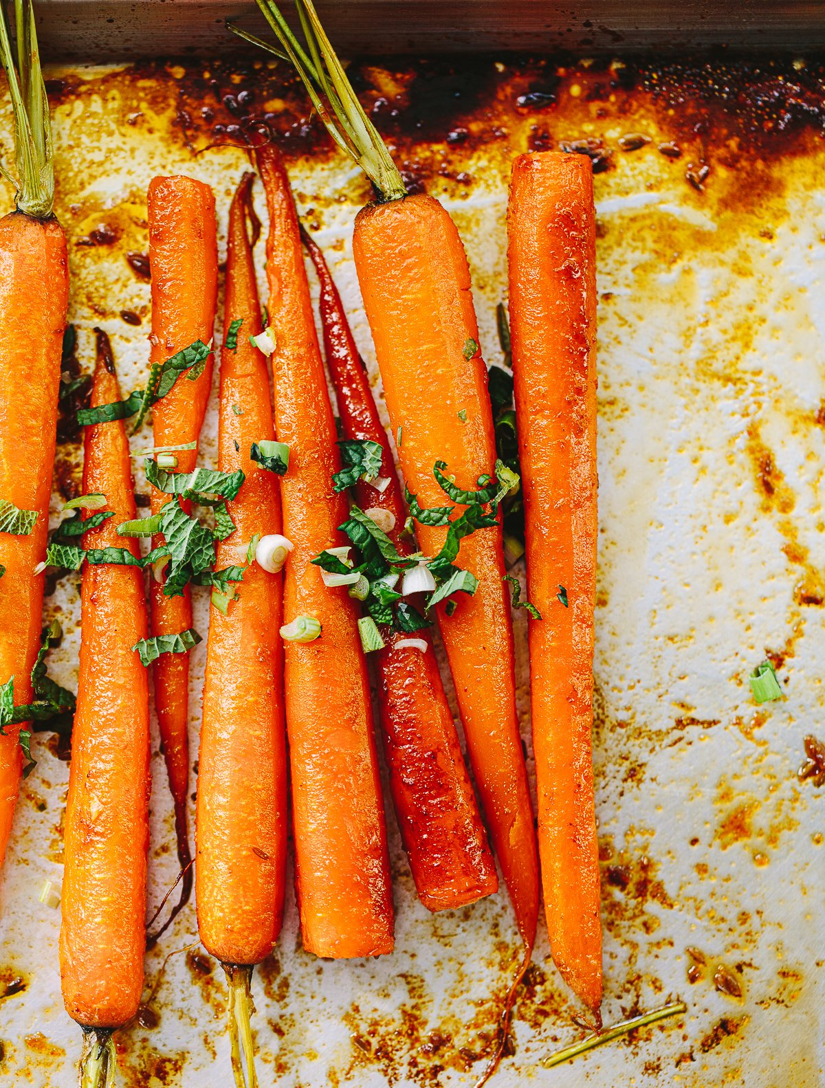 A bunch of roasted carrots on a sheet pan, topped with mint, lime and feta cheese.