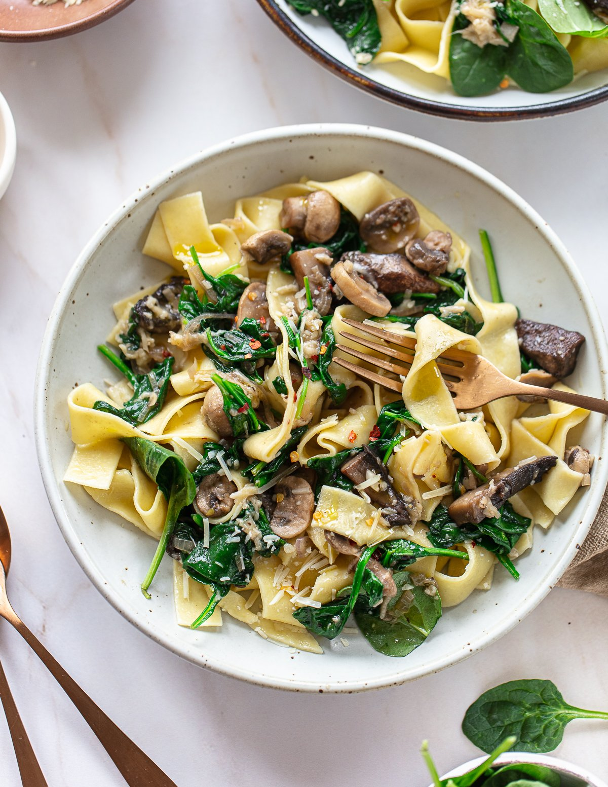 A bowl of pappardelle pasta noodles with a fork on the side, topped with sauteed mushrooms, spinach and Parmesan cheese