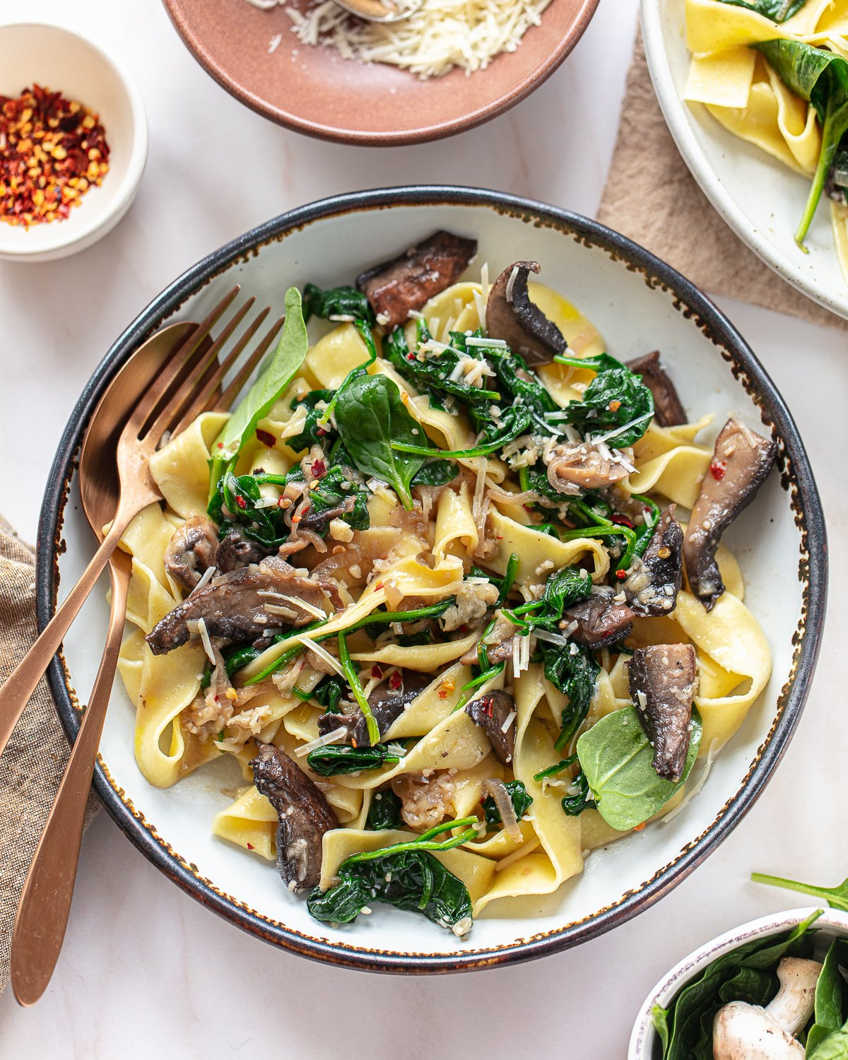 A round bowl with a serving of mushroom spinach pasta, with a fork and spoon on the side of the bowl.