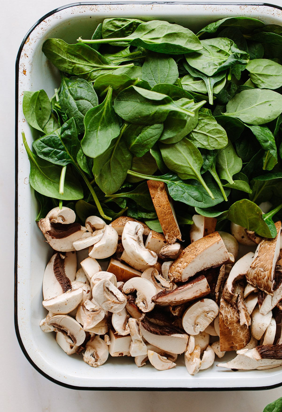 A rectangular enamel tray with raw button mushrooms and a pile of fresh spinach leaves.