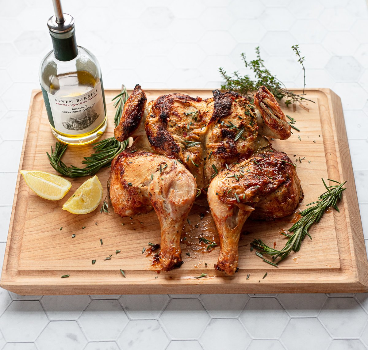 An image of a golden brown roasted butterflied chicken on a cutting board with wedges of lemon and rosemary herb sprigs.