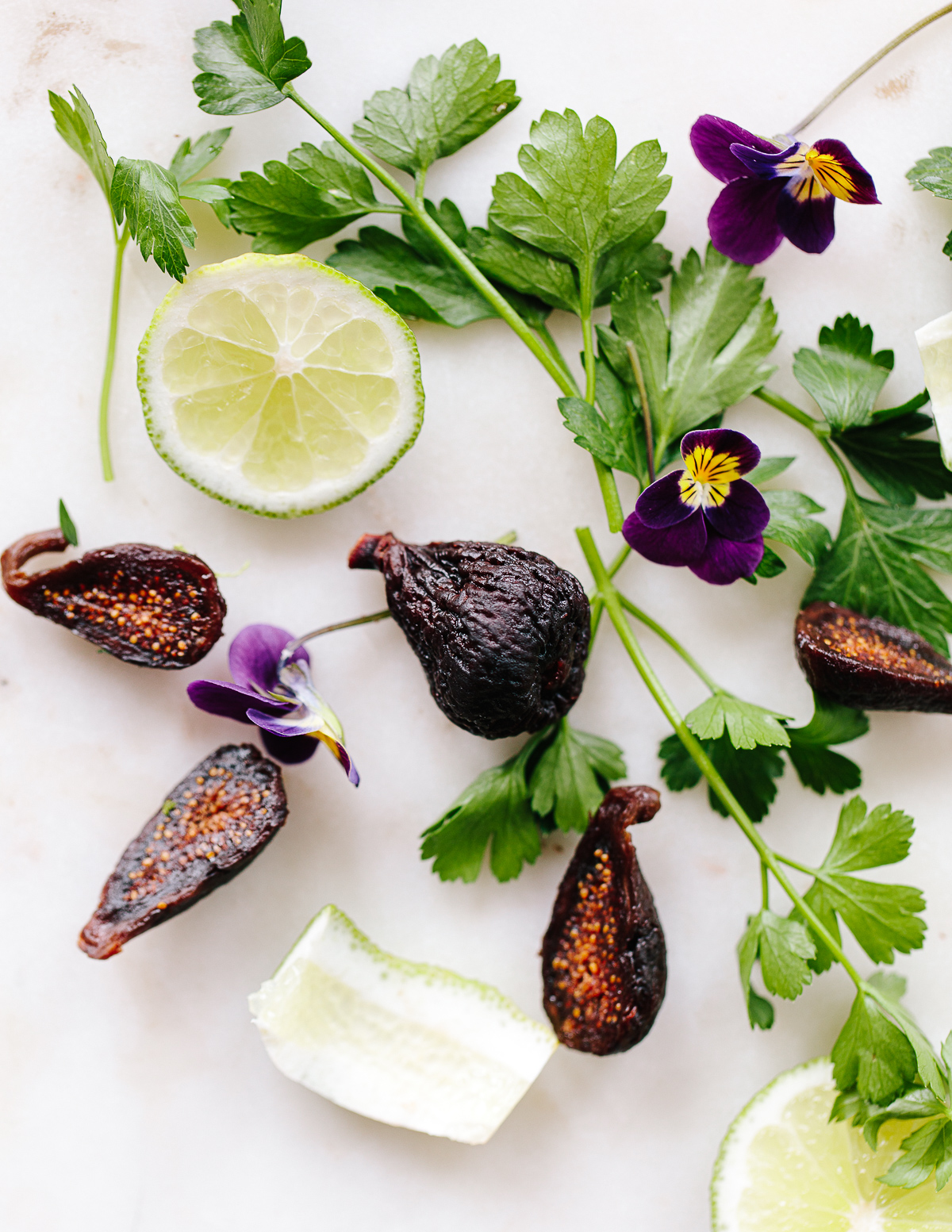 An image of dried figs, fresh lime slice, violet flowers and parsley leaves on a white surface.