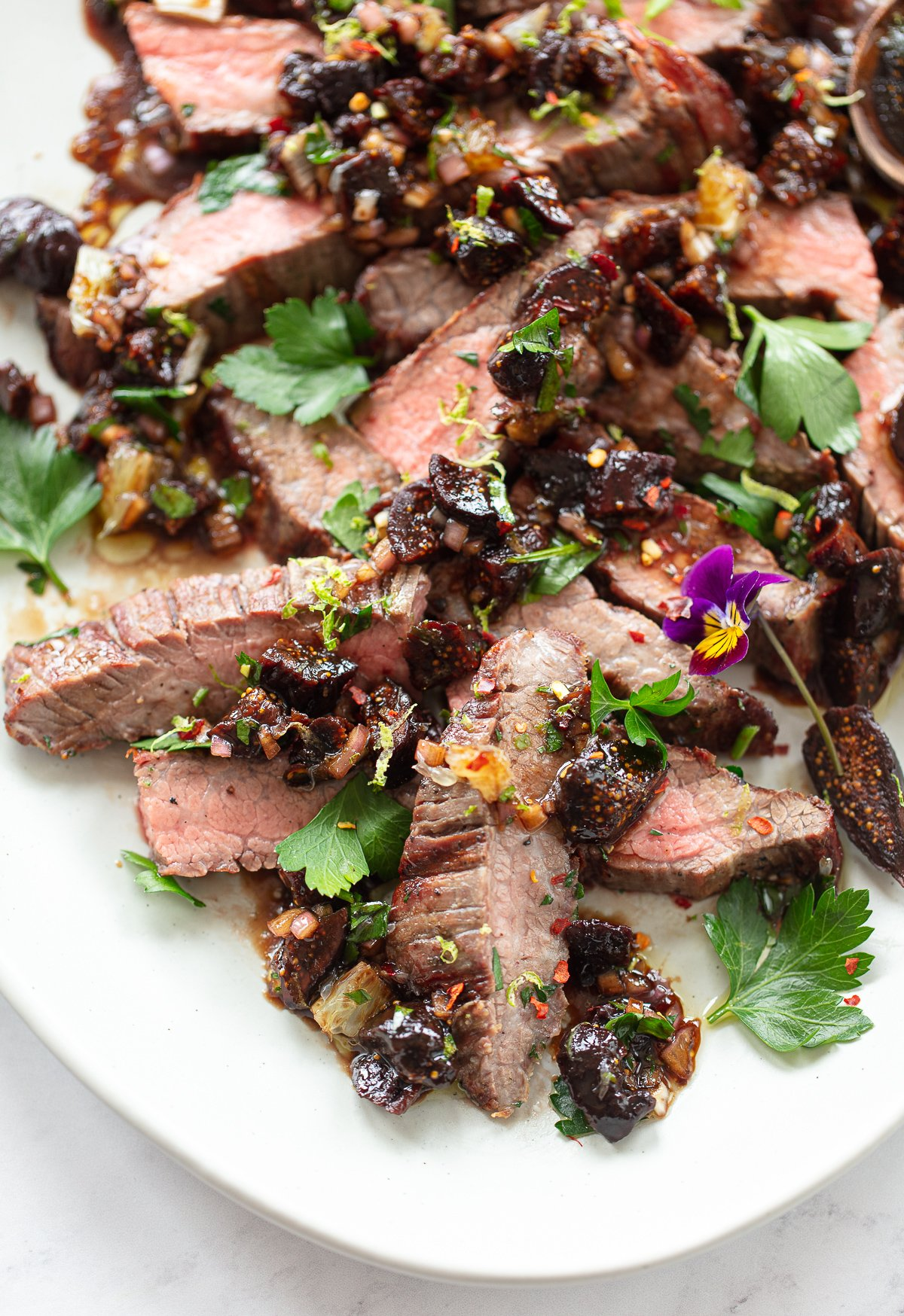 A close up image of sliced medium rare grilled steak topped with a dried fig sauce and fresh parsley.