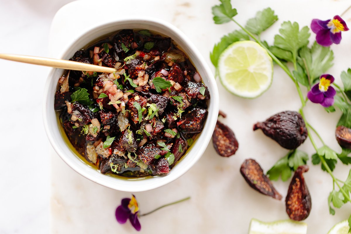 An image showing a bowl of chopped dried figs mixed with olive oil, lime and fresh parsley leaves.
