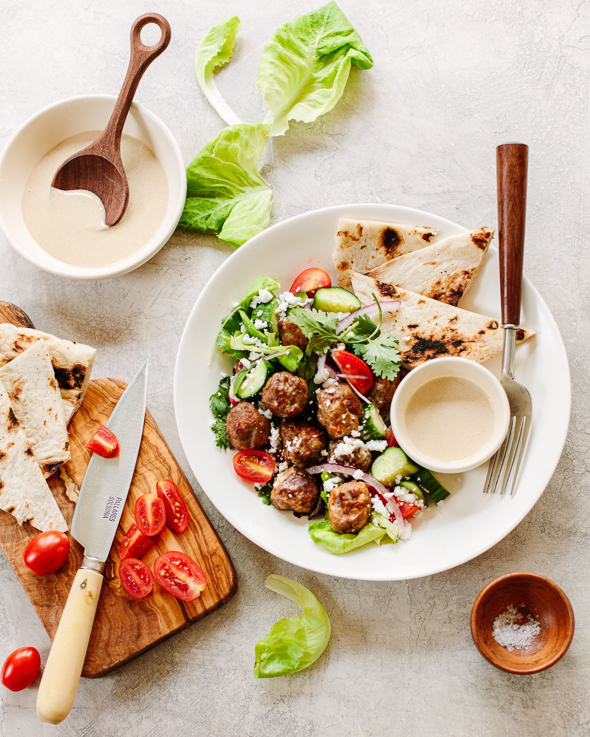 Chicken Gyro Meatballs on a plate with cucumber, tomato, tahini sauce and pita bread.