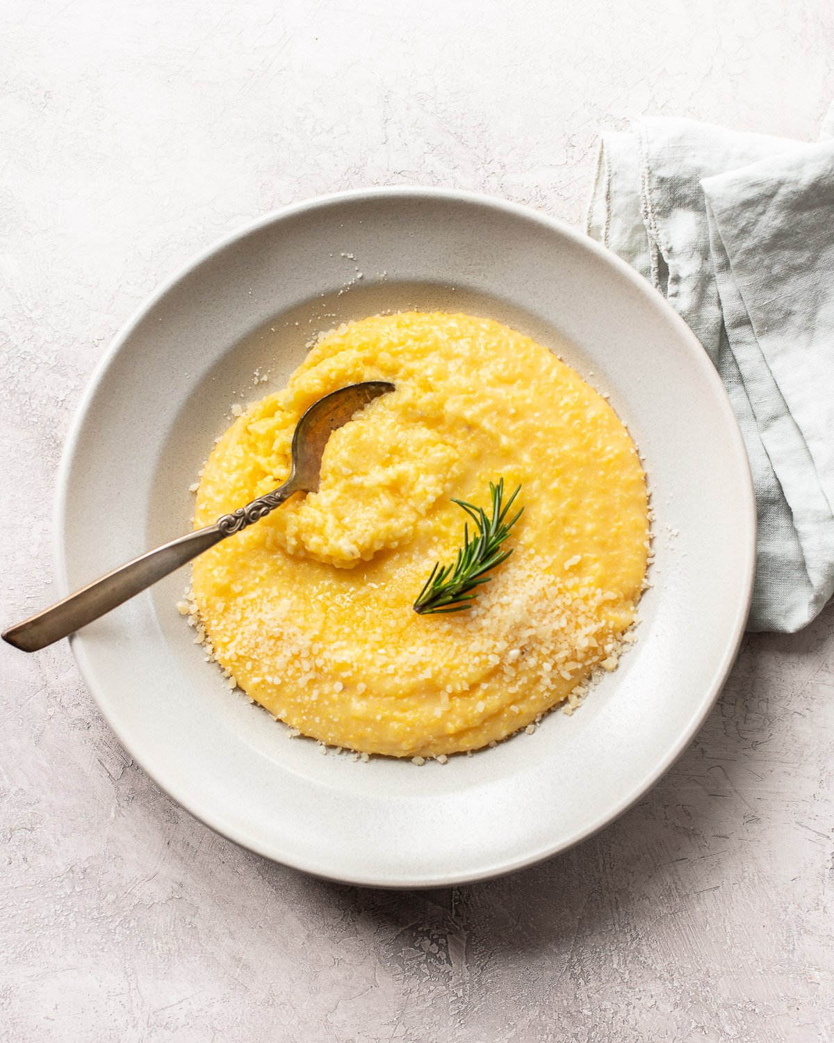 An overhead photo of a white bowl and a spoon dipping into creamy polenta topped with grated Parmesan cheese and a sprig of rosemary on top.