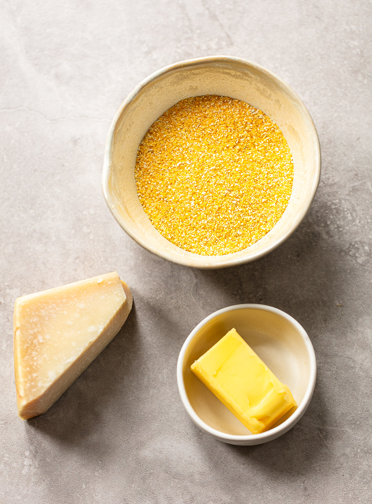 Photo showing the ingredients for making homemade polenta, with a bowl of cornmeal, chunk of Parmesan cheese and butter.