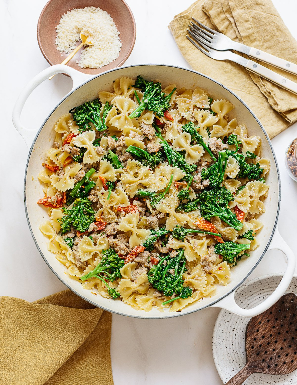 A photo of a white braising pan full of cooked bow tie pasta in a sausage and broccoli sauce.
