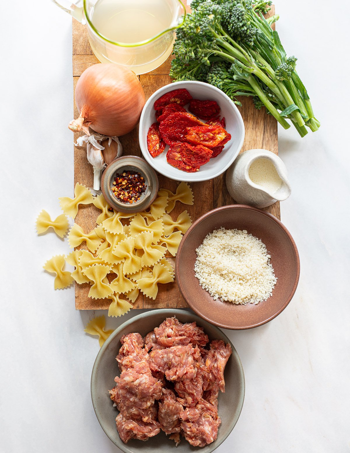 An overhead photo of ingredients laid out on a cutting board, with bow tie pasta, raw sausage meat, dried tomatoes, grated cheese and broccolini.