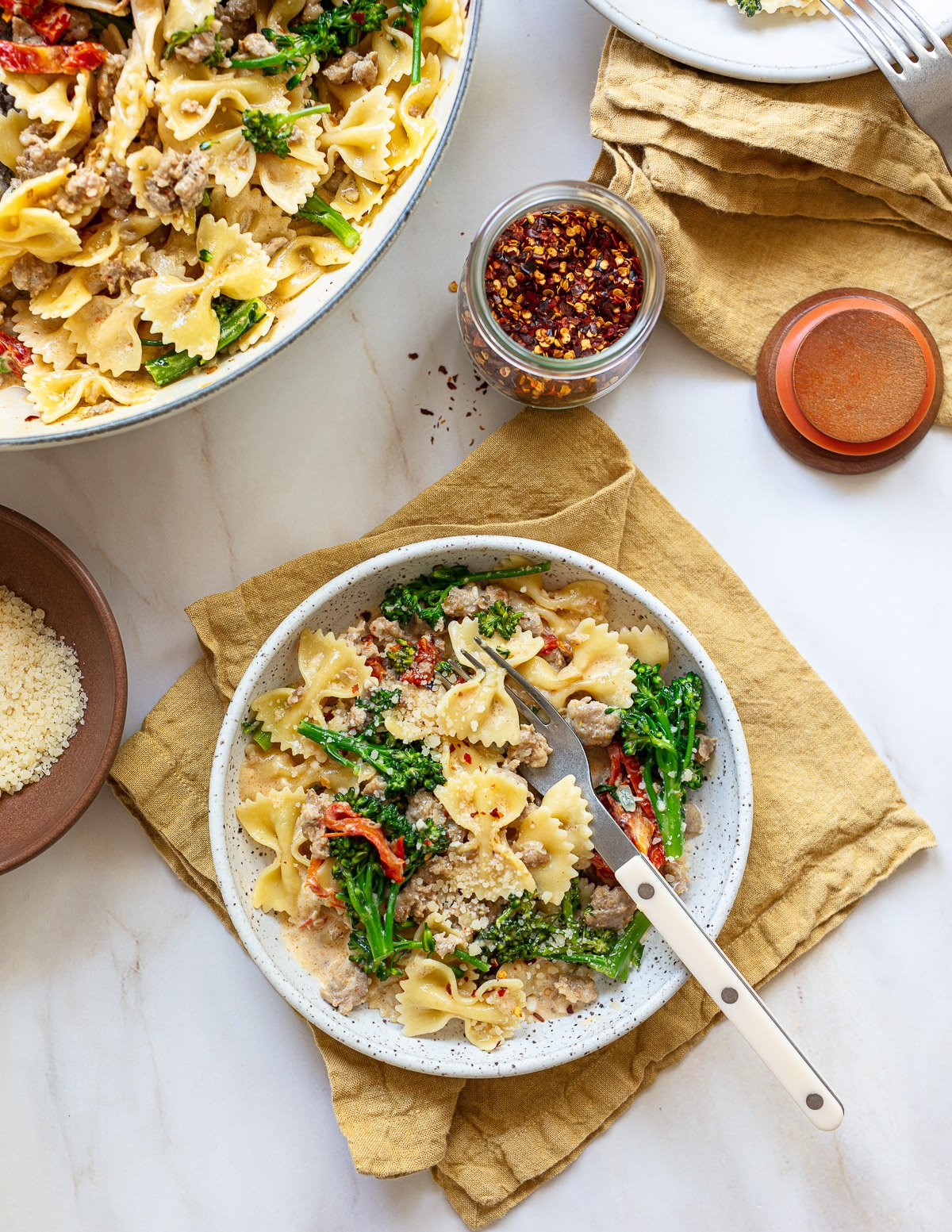 A photo of a bowl  and a fork serving farfalle pasta with a sausage and broccoli sauce, topped with grated cheese.