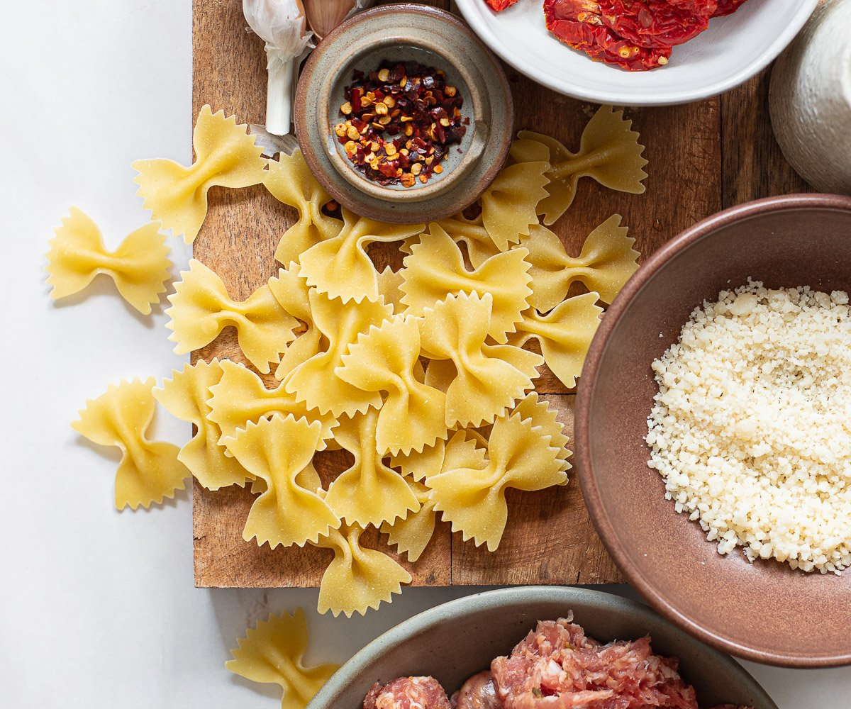 A close up of dried bowtie pasta on a prep board.
