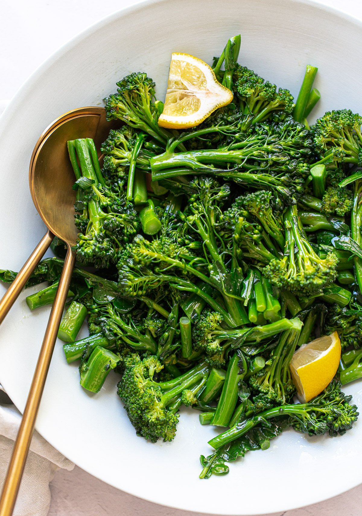Image - A round gray serving bowl with cooked broccoli sprouts and stems, with serving spoons and lemon wedges.