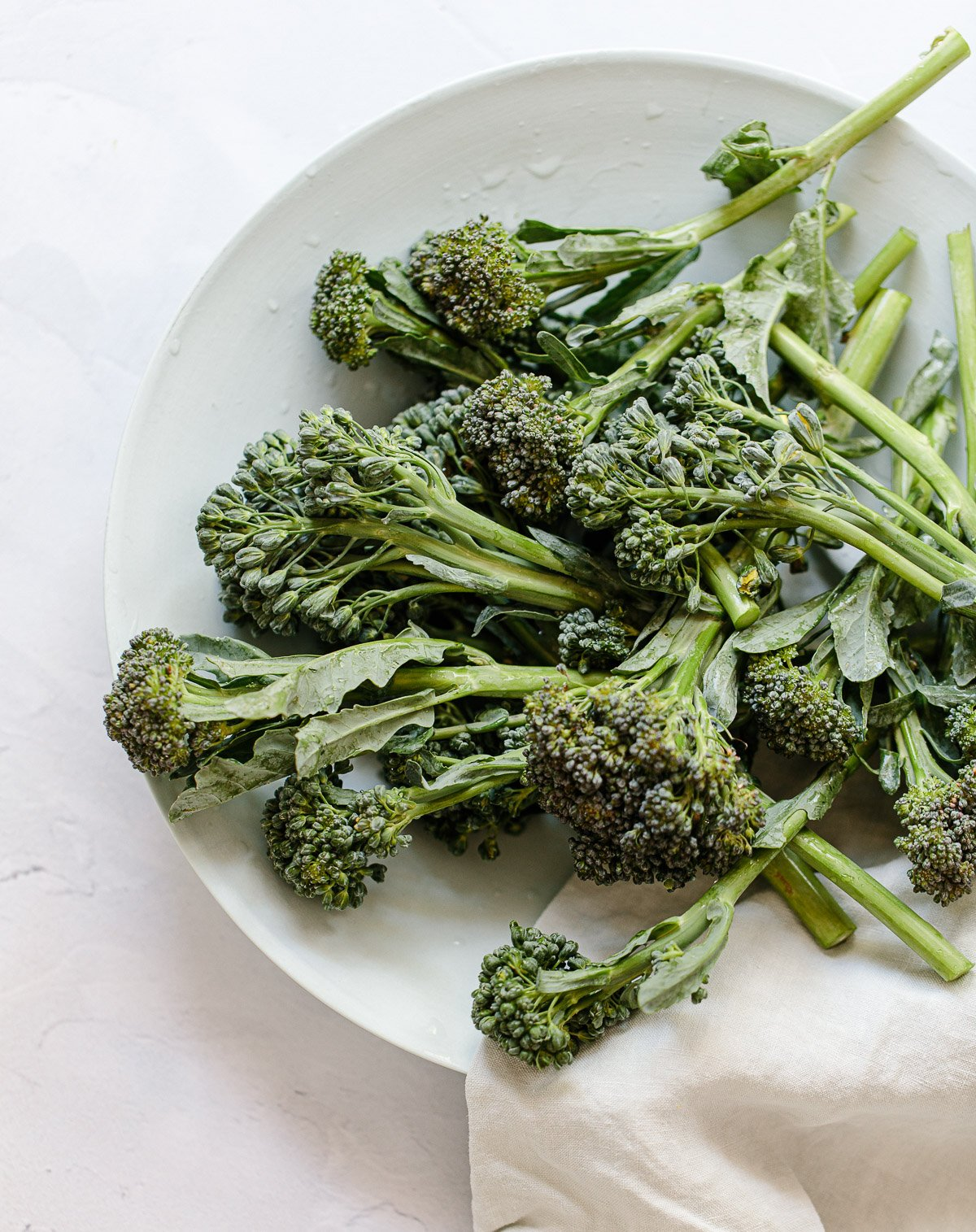 Image: Broccolini spears and florets arranged on a bowl with a napkin.