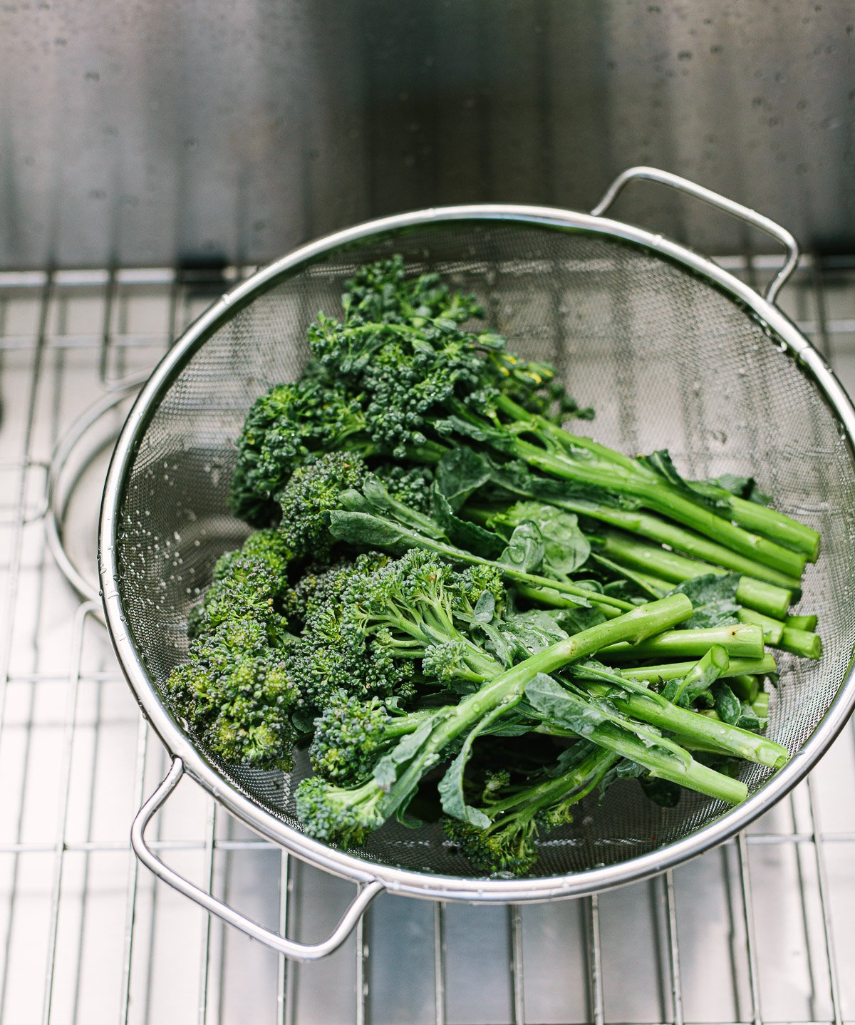 Image of broccolini in a wire mesh colander in a stainless steel sink.