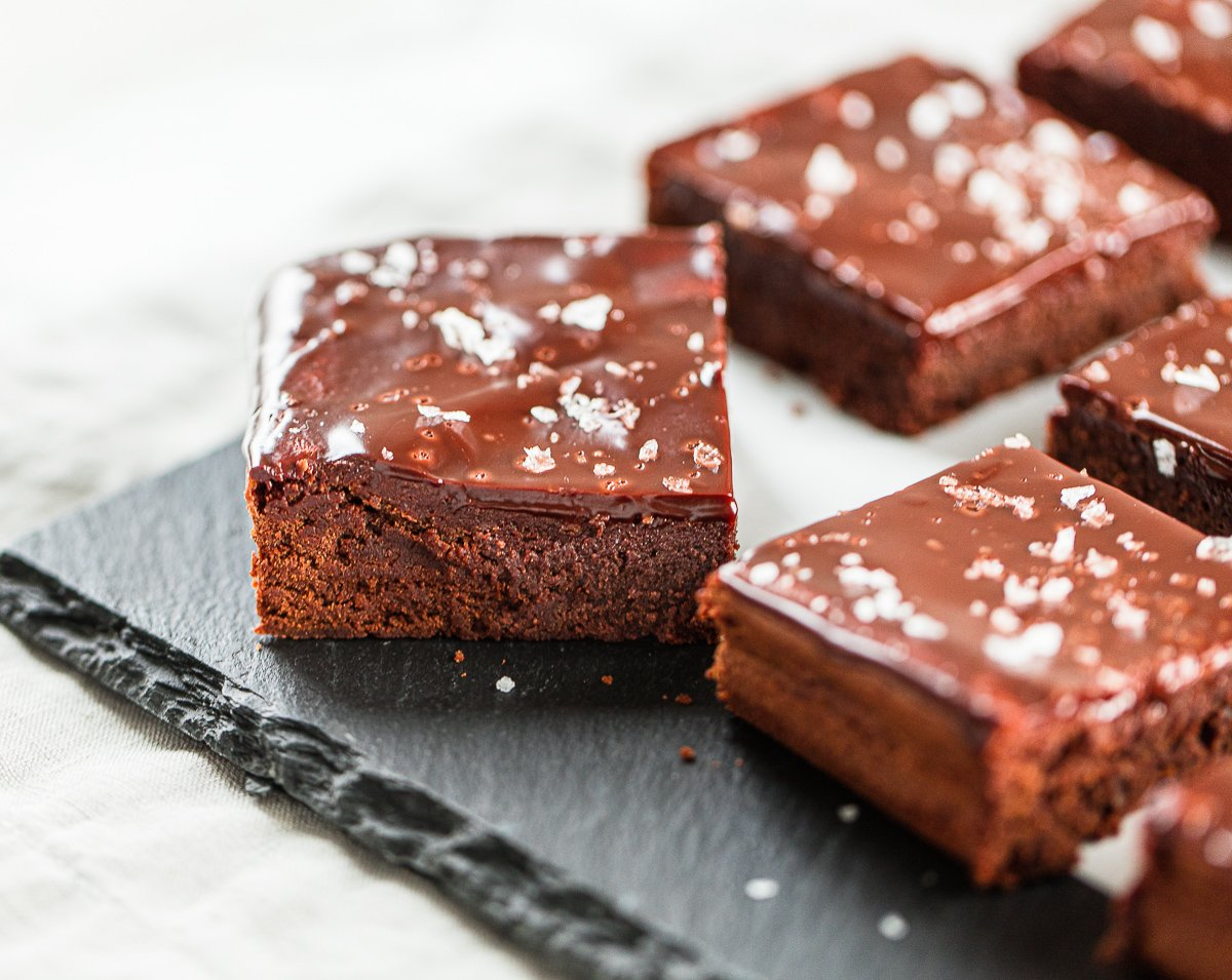 Sliced brownie squares on a slate board, topped with chocolate froting and flaked sea salt.