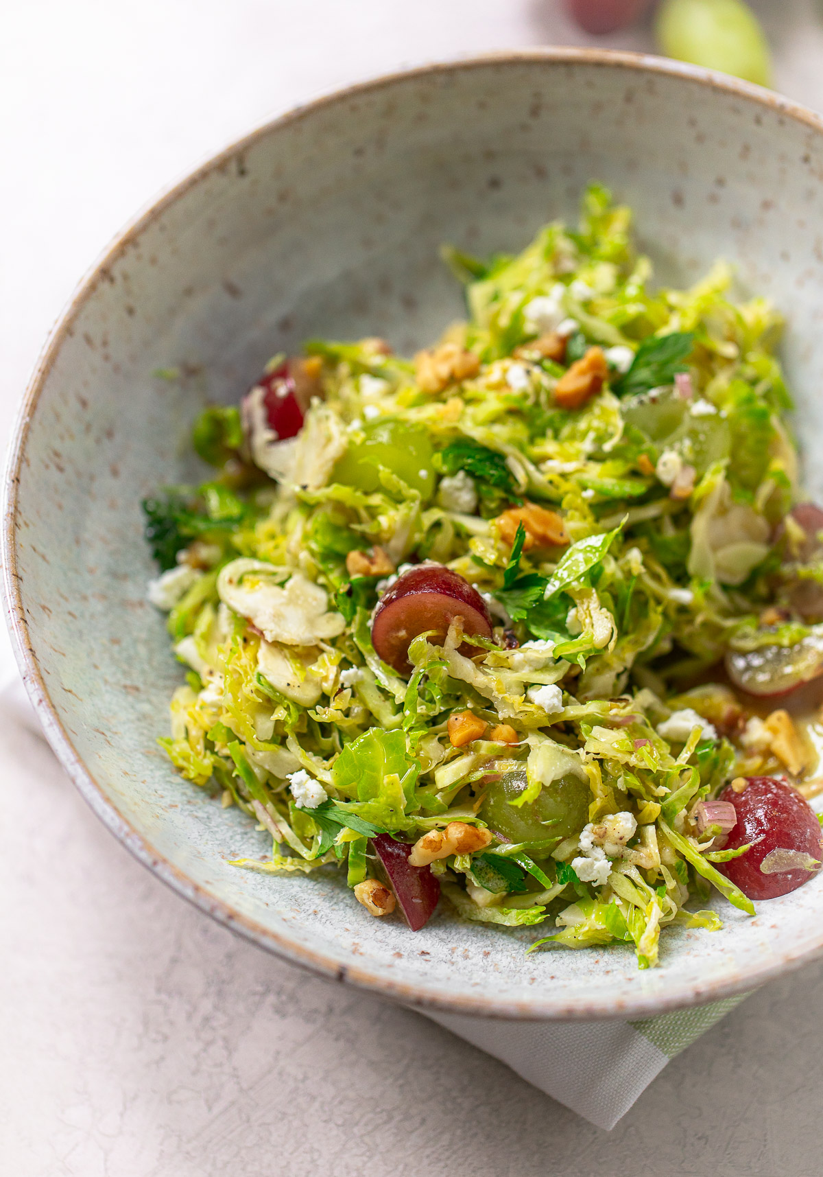 A close up of a bowl of shredded Brussels sprouts in a bowl with grapes, feta cheese and walnuts.