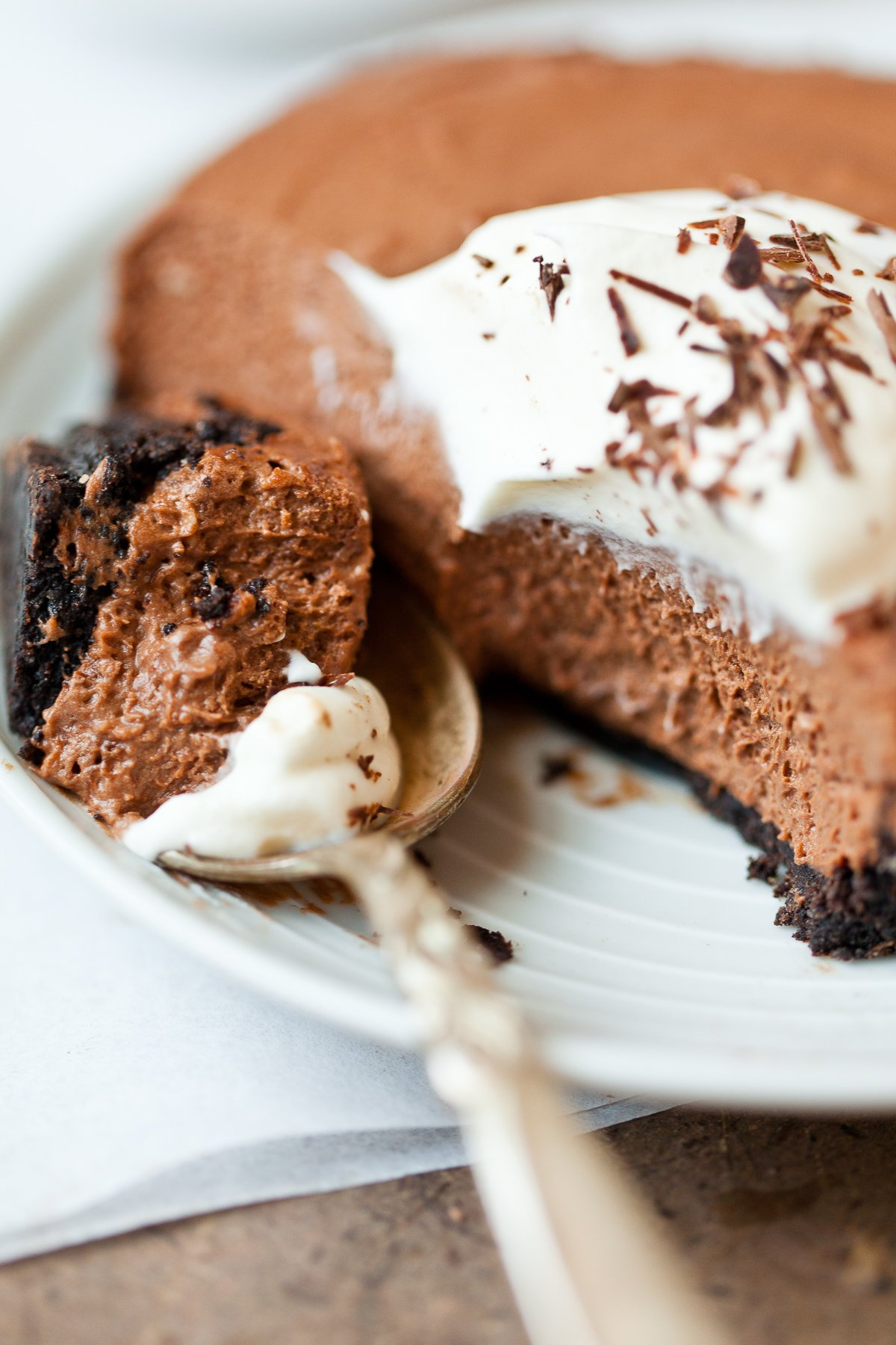 A close up photo of a frozen chocolate semifreddo dessert on a spoon with whipped cream and chocolate shavings.