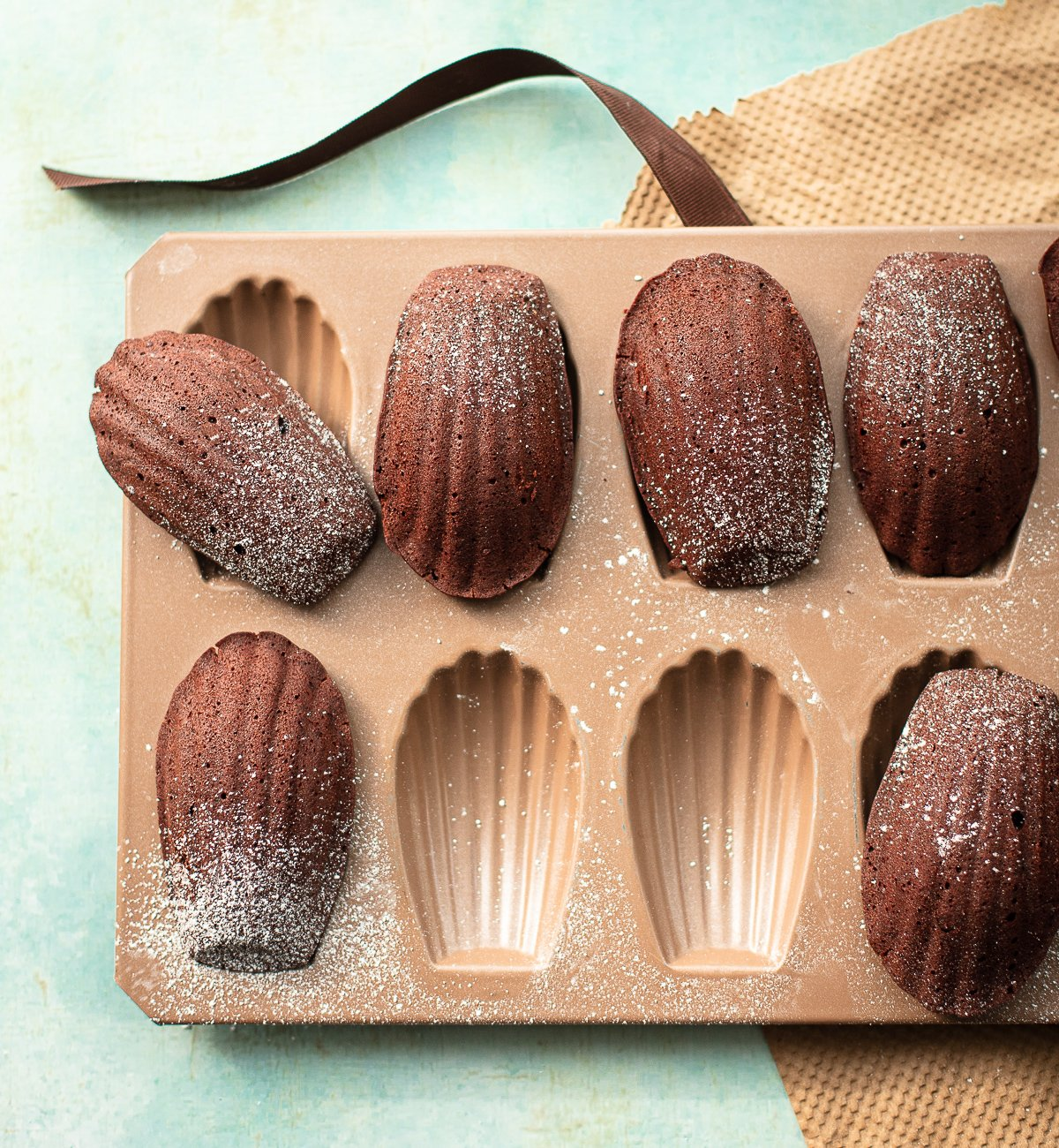 A image of baked chocolate madeleine cakes arranged in a madeleine baking pan.