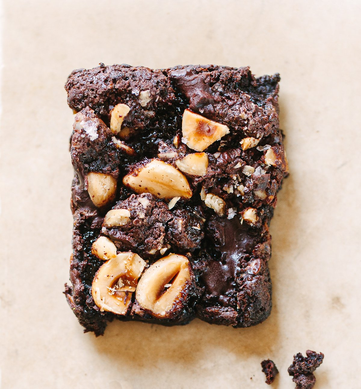 A close up picture of a a chocolate hazelnut brownie square, with gooey melted chocolate on top.