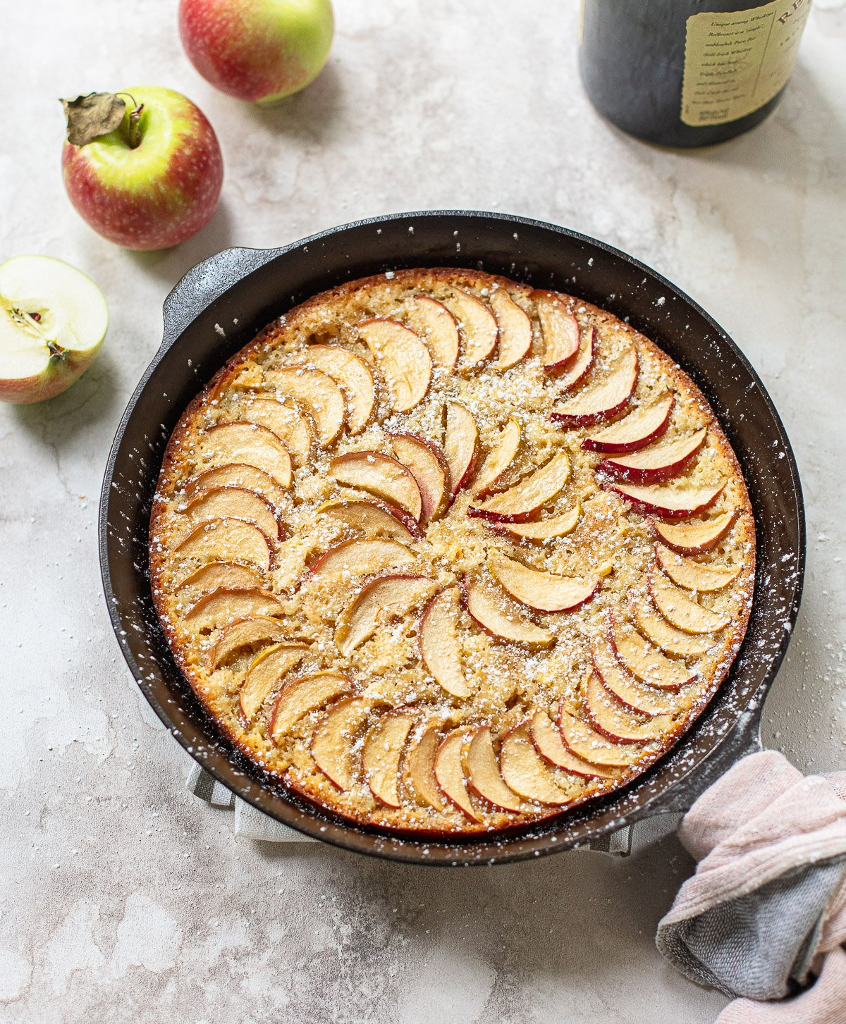 Photo of a black cast iron skillet with baked French apple cake, with sliced apples and powdered sugar on top.