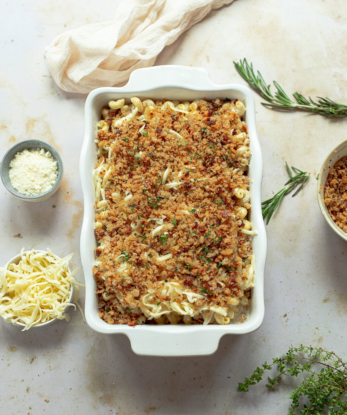 Image showing a white casserole dish filled with curly cavatappi pasta in a white creamy cheese sauce topped with toasted herbed breadcrumbs.