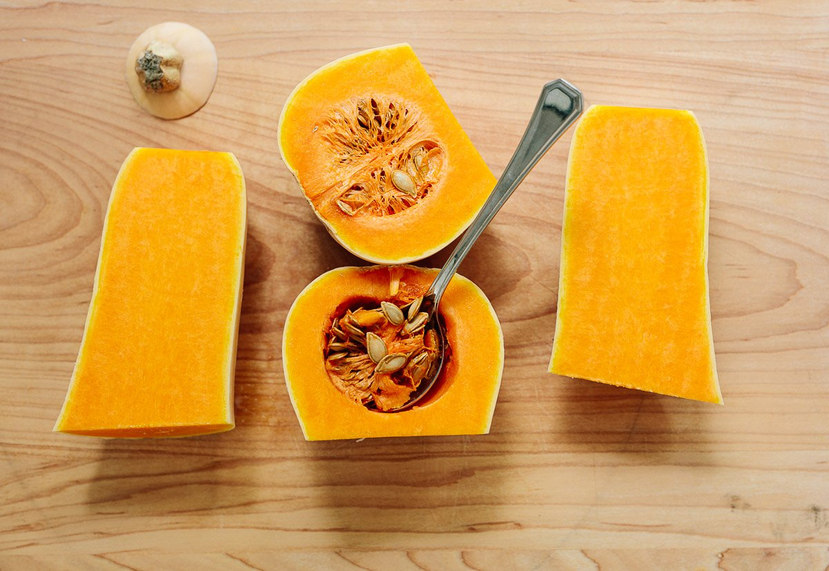 Image of cut open butternut squash on a cutting board, with a spoon scooping out the seeds.