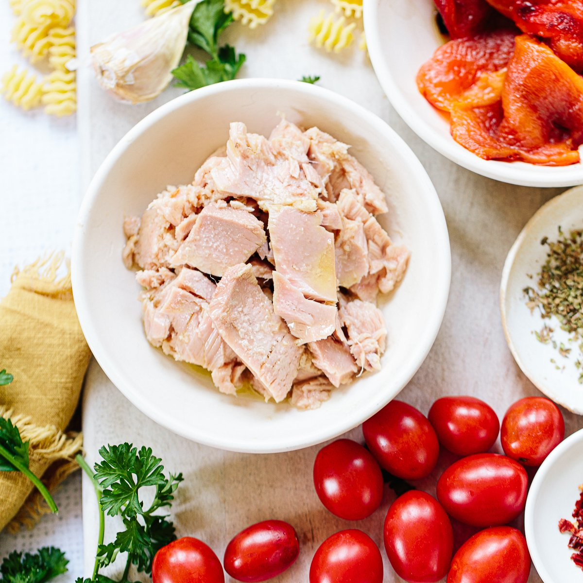 Close up photo of a bowl of canned tuna chunks in a bowl, surrounded by tomatoes, parsley and garlic.
