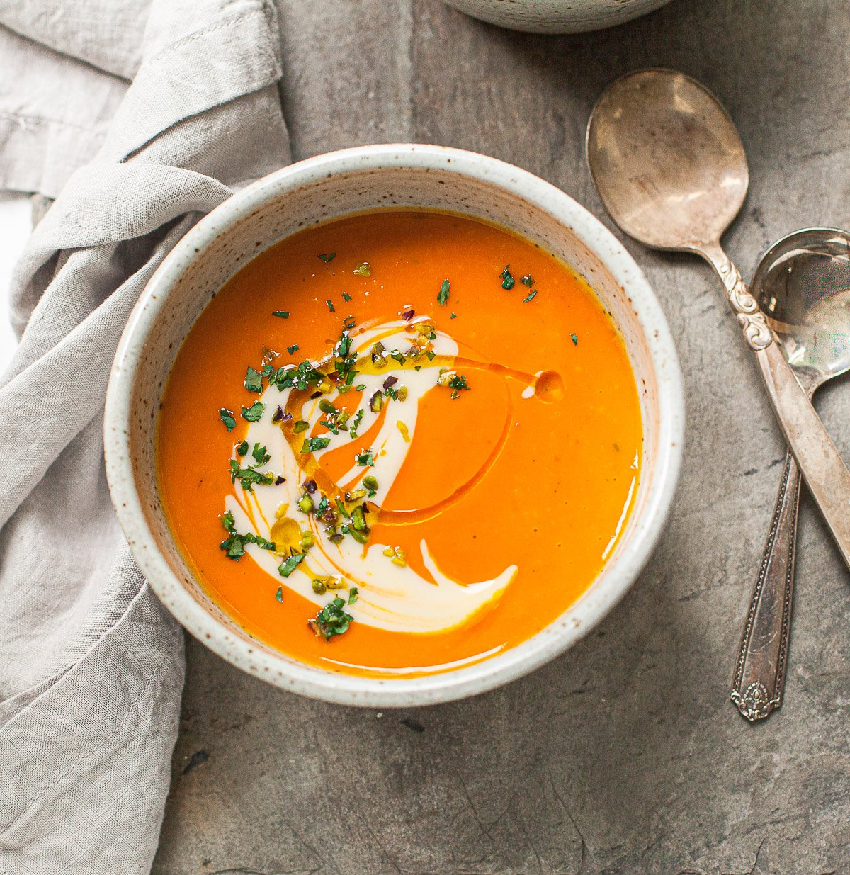 Image of a bowl of smooth butternut squash soup, topped with pumpkin seeds, herbs and a swirl of cream.